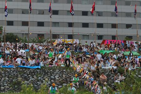 堤防に座る観客と、連なる屋台
